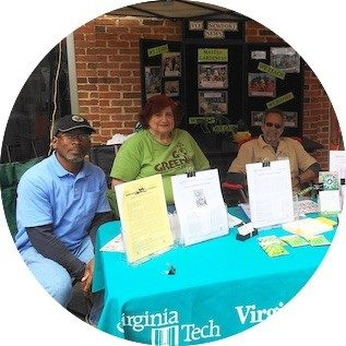 master gardeners sit at help desk with pamphlets on table in front of them