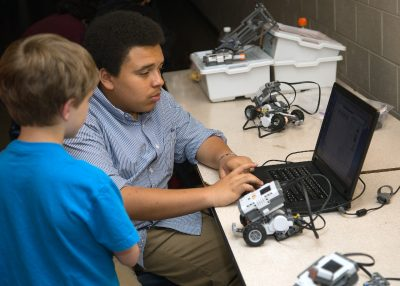 Maker coach Instructs student on the programming of robots.