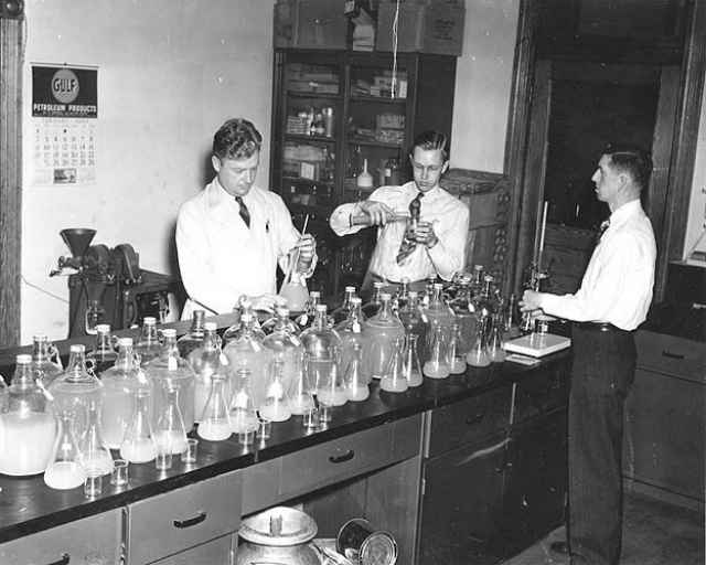Men work in a lab with jars and beakers in the 1940s.