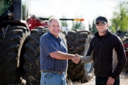Older man shakes hands with younger man. Tractor in background.